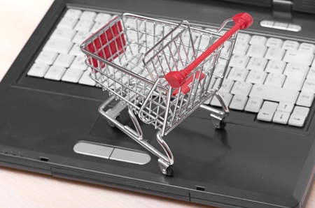 Online shopping  trolley on laptop isolated on white photo