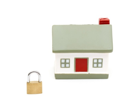 deadbolt: miniature house with lock isolated on white