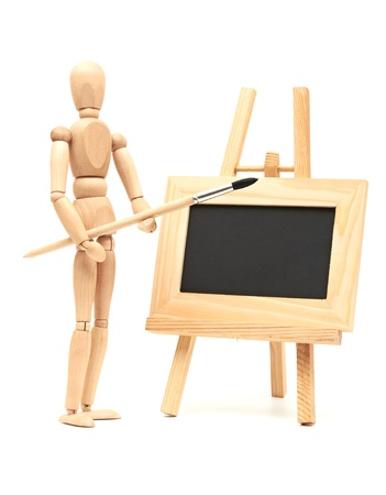 Wooden artist mannequin with brush in pose with wood frame photo