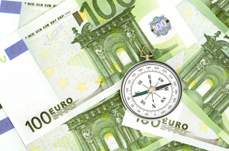 pioneering: many euro bank notes and a compass lie side by side