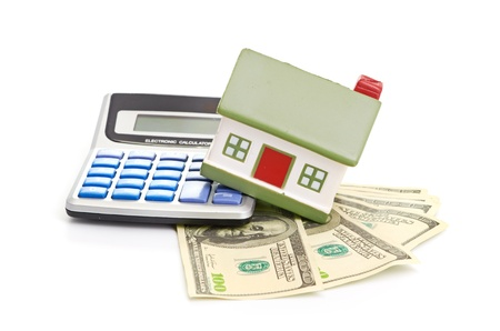 A model house sitting with a calculator and dollar bills on a white background photo