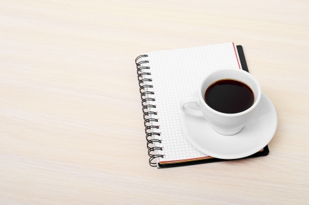 Coffee cup with note book on table Stock Photo