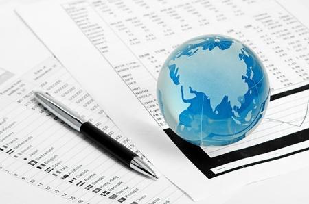 Glass globe and pen on finance chart photo