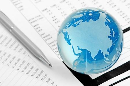 international monitoring: Glass globe and pen on finance chart Stock Photo