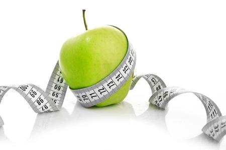 cinta de medir: Cinta métrica envuelta alrededor de una manzana verde como símbolo de la dieta