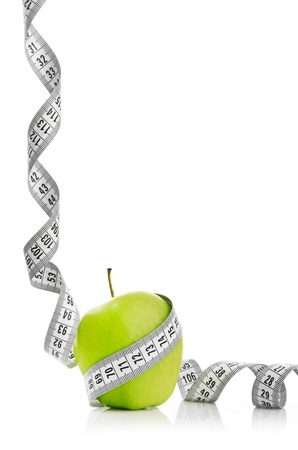 Measuring tape wrapped around a green apple as a symbol of diet.