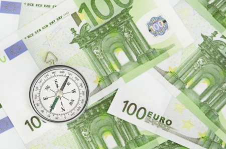 pioneering: many euro bank notes and a compass Stock Photo