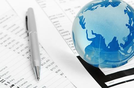 international monitoring: Glass globe and pen on finance background