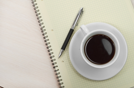Coffee cup with note book on table photo