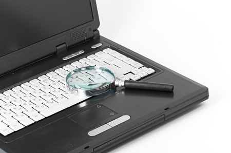 Laptop with a magnify glass on white photo