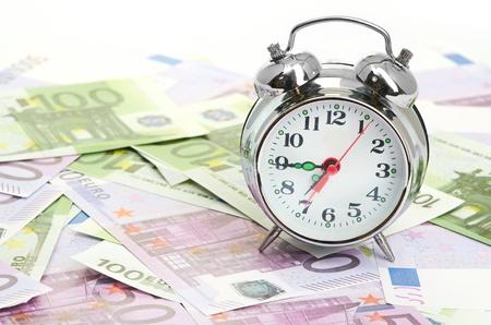 clockwise: Alarm clock for euro banknotes Stock Photo