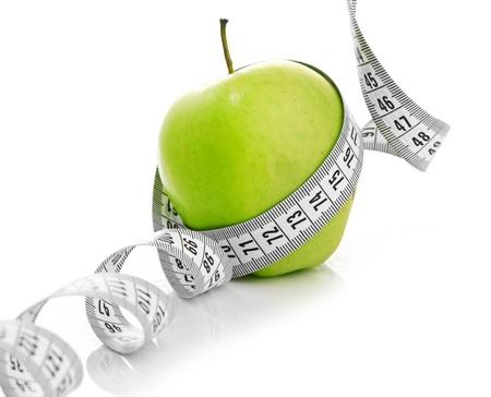 huincha de medir: Cinta m�trica envuelta alrededor de una manzana verde como s�mbolo de la dieta