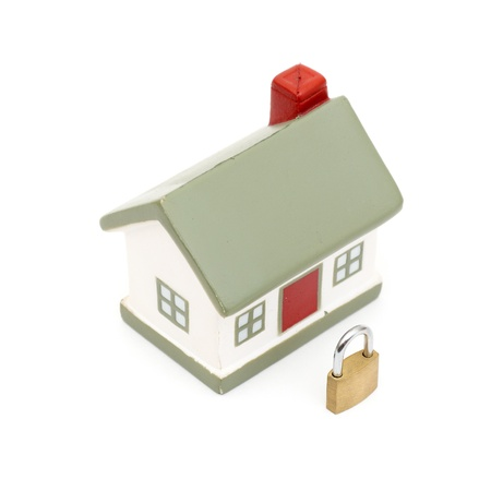 miniature house with lock isolated on white photo