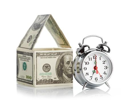 casa hecha de dólares y reloj de alarma aislado en el fondo blanco