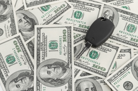 consumerism: Car Key on dollar background Stock Photo