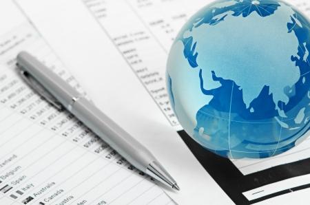 international monitoring: Glass globe and pen on finance Stock Photo