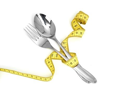 cinta metrica: Cuchara de acero y una cinta de medici�n y tenedor aisladas sobre fondo blanco Foto de archivo