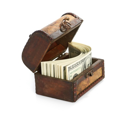 Dollar-bills in the old wooden treasure chest isolated on white background photo