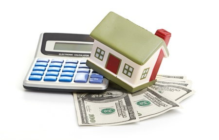 calculating: house sitting with a calculator and dollar Stock Photo