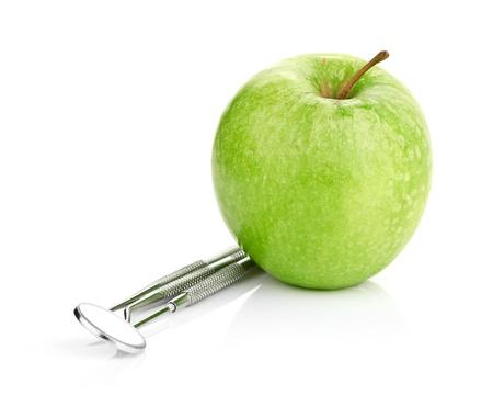 青リンゴ、白で隔離される歯科用ツール