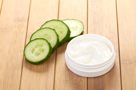 face mask with cucumber slices, white wood background photo