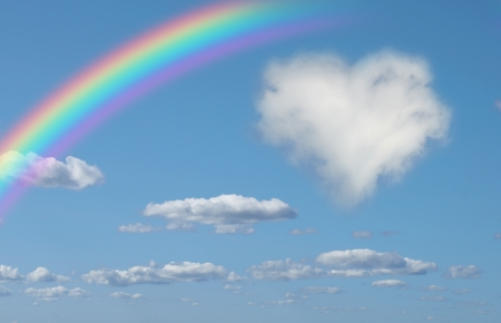 Fluffy cloud of the shape of heart and rainbow in the sky photo