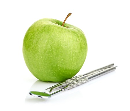 clinician: Green apple and dental tools isolated on white