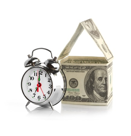 house made of dollars and alarm clock. Isolated on white background. photo