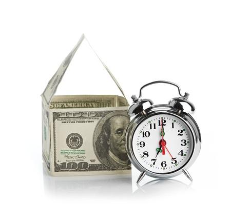 punctual: casa hecha de dólares y reloj despertador. Aislado sobre fondo blanco. Foto de archivo