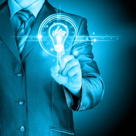 the cleaver: Business man touching light of idea Stock Photo