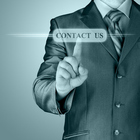 Businessman pushing CONTACT US sign photo
