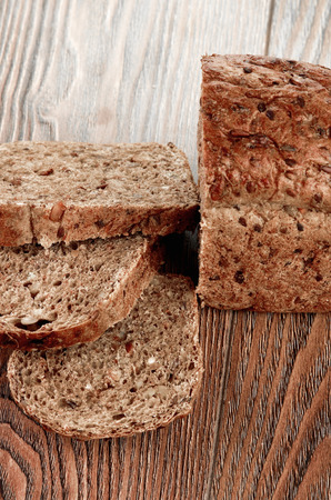 Slices of brown bread on a wooden table photo