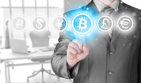Choosing bitcoins, businessman pressing touch screen button  Stock Photo