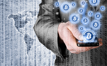 Hand with mobile smart phone and bitcoin symbol Stock Photo