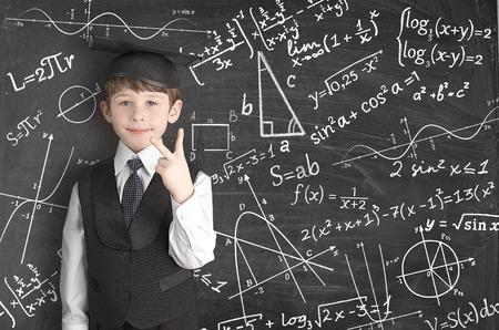 boy near blackboard with formulas photo