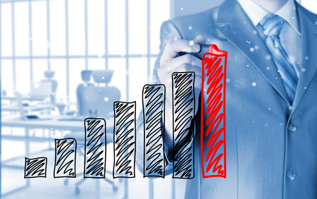 Business man drawing a growing graph photo