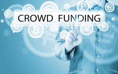 Businessman pushes virtual crowd funding button photo