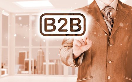 businessman pointing to word B2B, business-to-busines, written in the foreground Stock Photo