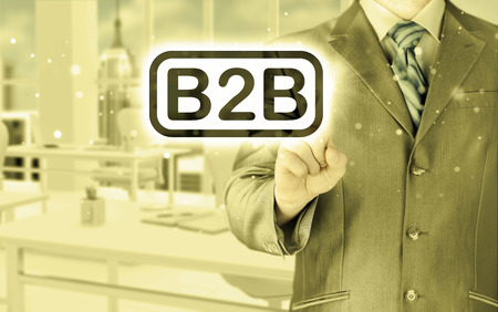 businessman pointing to word B2B, business-to-busines s, written in the foreground photo
