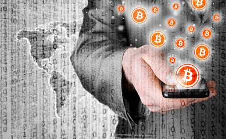 Hand with mobile smart phone and bitcoin symbol Imagens