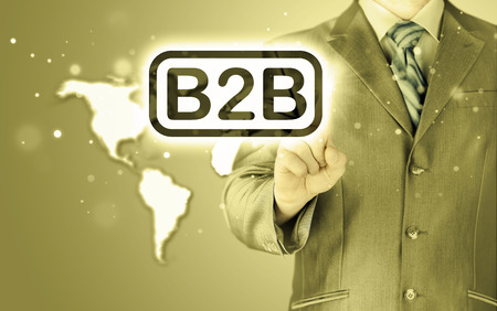 businessman pointing to word B2B, business-to-busines s, written in the foreground Stock Photo