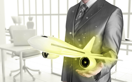 Businessman with airplane over his hand photo
