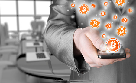 net trade: Hand with mobile smart phone and bitcoin symbol Stock Photo