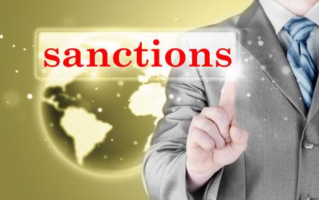sanctioned: businessman pressing sanctions button on virtual screens