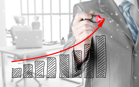 future earnings: Business man drawing a growing graph Stock Photo