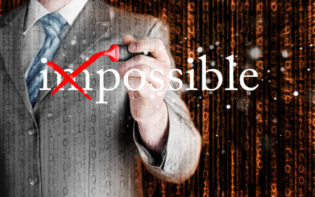 Businessman Hand turning the word Impossible into Possible with red marker photo