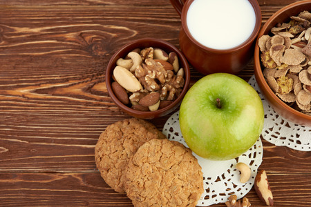 Breakfast meal of apple , mix nuts , cookies and milk  photo