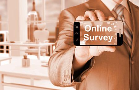 Businessman showing business concept on smartphone  - Online Survey Stock Photo