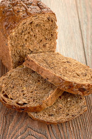 Slices of brown bread on table photo