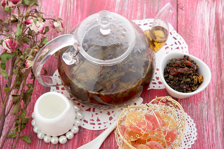 barbarum: cinnamon and fruit drink in glass teapot on wooden background